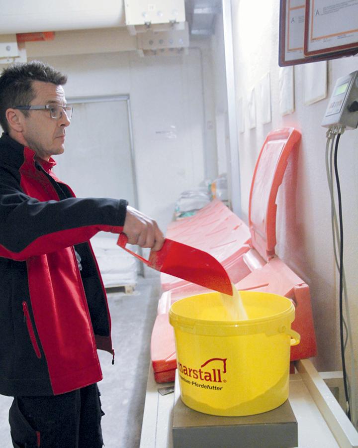 Unser Kollege steht an einer Waage und wiegt die exakte Menge an Mineralien, Spurenelementen und Vitaminen für die Pellets ab.