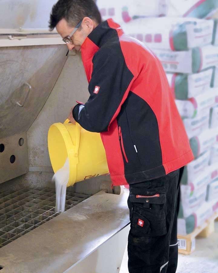 Die abgewogenen Mineralien, Spurenelemente und Vitamine werden in ein Becken geschüttet, von wo aus sie per Luftdruck in den Mischer gelangen